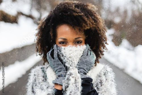 Afro hair young woman wearing wool scarf under the snow in winter