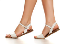 White Leather Flat Sandals On Female Legs On White Background