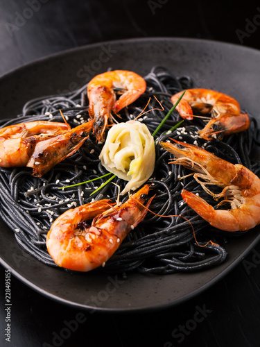 Photo  Black spaghetti with shrimps, ginger and sesame seeds