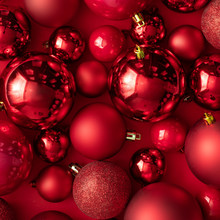 Red Christmas Baubles Decoration On Red Background. New Year Party Background. Minimal Style.  Flat Lay.