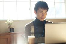 パソコンに向かい仕事をする20代男性
