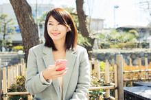 屋外で携帯電話を使う20代女性