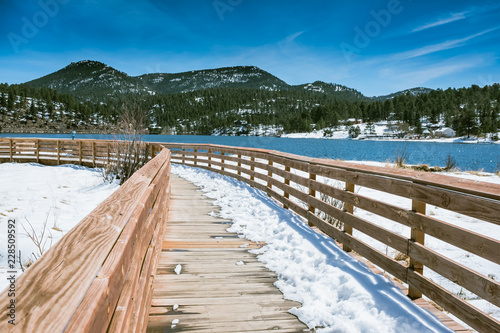 VIEW WOODEN WALK WAY WITH BACKGROUND OF BRIGHT BLUE SKY AND  SNOW ON GROUND OF E Canvas-taulu