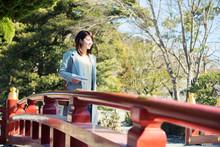 橋を渡る笑顔の20代女性