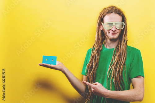 Fotografie, Obraz  Happy man holding a retro cassette tape on a yellow background