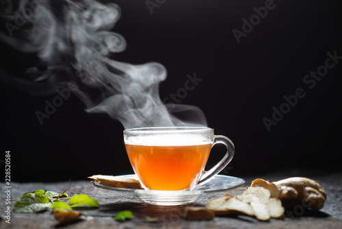 Staande foto Thee Hot Ginger tea in a glass on wood background.Hot drink . Copy space.