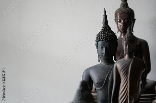 select focus of vintage black ancient buddhas statue in the middle of other buddhas statue