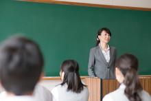 教室で授業を受ける学生と女性教師