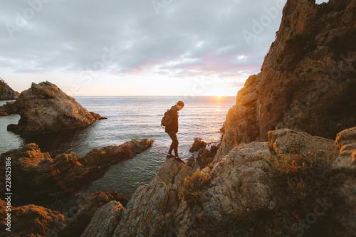 Unrecognizable person standing on cliff near sea