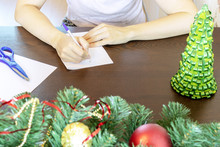 Hands Of A Woman Sitting By The Table And Writing Christmas Wishes On A Card, Letter