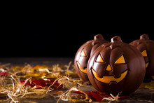 Chocolate Halloween Pumpkins On Wooden Table And Black Background. Copyspace