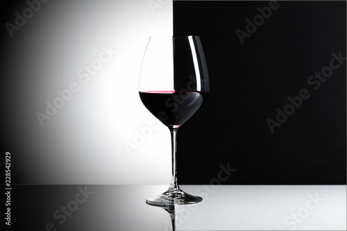 Glass of red wine on a reflexive background.