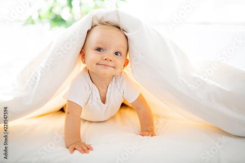 Fototapeta Cute baby girl lying on white sheet at home obraz