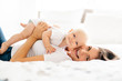 canvas print picture - mother with baby on bed having good time