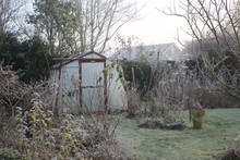 Landscape Of Frozen Winter Garden In Heavy White Frost With Misty Pane Glass Greenhouse, Icy Lawn And Plants Trees In Spring Seasonal Frosty Weather In Norfolk England