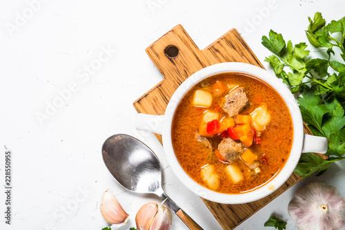 Goulash soup on white stone table top view.