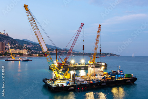 Crane vessels on water at sunset Fototapeta