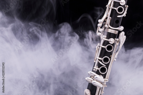 Foto A black clarinet with silver plated keys in smoke on a black background