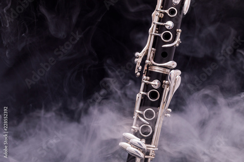 Leinwand Poster A black clarinet with silver plated keys in smoke on a black background