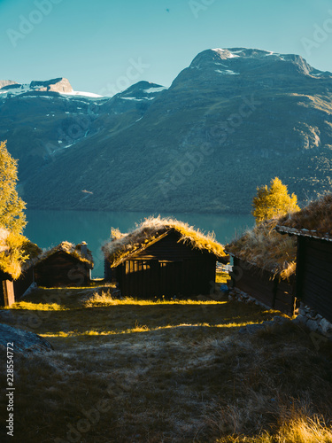 Fotobehang Groen blauw Traditional scandinavian old wooden houses with grass roofs near lovatnet lake, Sogn og Fjordane county, Norway