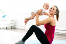 A Portrait Of Beautiful Young Mother In Sports Wear With Her Charming Little Baby In Training Session