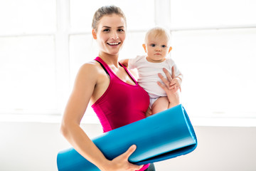 Fototapeta A Portrait of beautiful young mother in sports wear with her charming little baby in training session