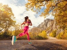 Young Woman Running On A Mountain Road In The Beautiful Nature. Girl Runner In Sneakers Jogging Workout Outdoors. Weight Loss Concept. Healthy Lifestyle.