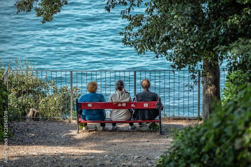 Anziani seduti su una panchina fronte mare, mentre parlano e pensano alla vita v Canvas Print