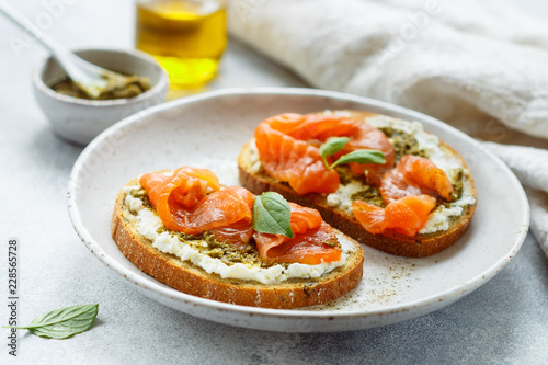 Bread toast with salted salmon, pesto sauce and cream cheese (ricotta). Gourmet snack. selective focus