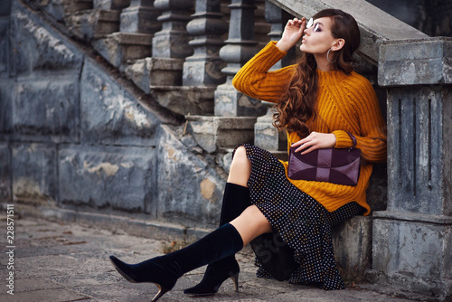 Outdoor full body fashion portrait of young beautiful woman wearing color sunglasses, stylish orange sweater, polka dot skirt, trendy sock boots, holding small purple bag, posing in street. Copy space