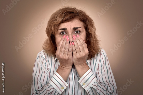 Fotografía  Portrait of  scared middle-aged woman with hands on her face