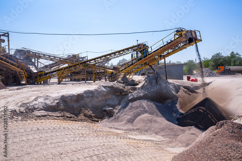 Photo Crushing machinery, cone type rock crusher, conveying crushed granite gravel stone in a quarry open pit mining