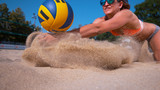 CLOSE UP: Smiling female volleyball player dives and strikes ball with her hands