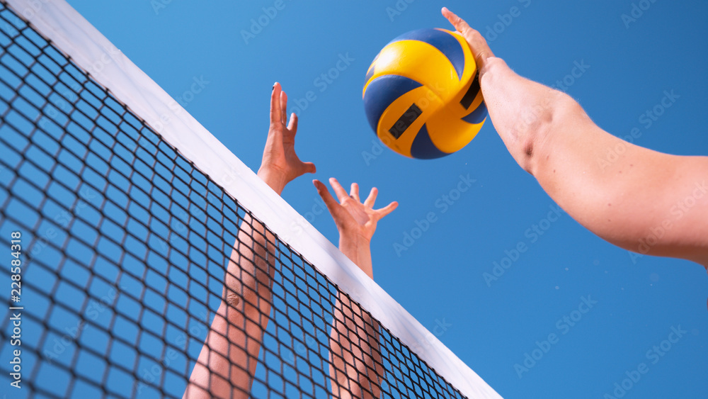 Fototapeta CLOSE UP: Unrecognizable young female' hands playing volleyball at the net.