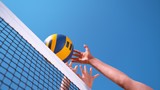 CLOSE UP: Unrecognizable female volleyball player spikes the ball past the block