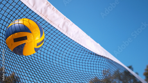 Obraz COPY SPACE: Ball gets caught in a black and white net during volleyball game. - fototapety do salonu