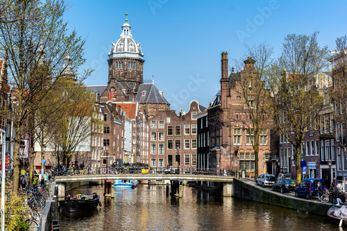 In de dag Centraal Europa AMSTERDAM, NETHERLANDS - APRIL 11, 2018: St. Nicholas Church and Amsterdam canal with typical dutch houses. St. Nicholas Church is the city's primary Roman Catholic church.