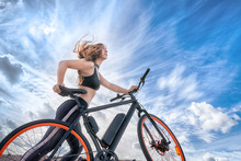 Athletic Girl With Hair Flying In The Wind Leading Electric Bike.