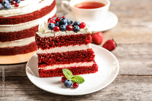 Plate with piece of delicious homemade red velvet cake on wooden table