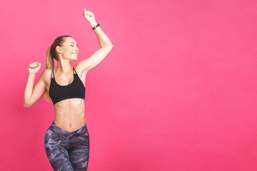 Gubitak kilograma fitness žena skakanje od radosti. Mladi sportski kavkaski ženski model izoliran na ružičastoj pozadini.