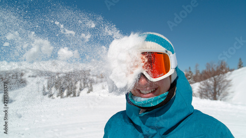 Fotografie, Obraz CLOSE UP: Excited girl wearing ski goggles gets hit in the head by snowball