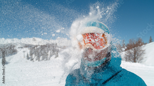 Fotografía  CLOSE UP: Smiling girl wearing ski goggles gets hit in the head by a snowball