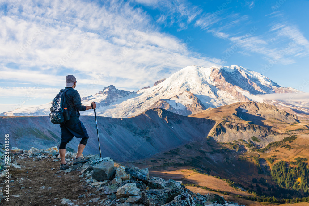 Fototapety, obrazy: A hiker looking at Mount Rainier with hiking poles in his hand