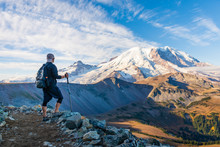 A Hiker Looking At Mount Rainier With Hiking Poles In His Hand