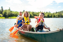 Family In A Canoe On A Lake Having Fun