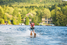 Child Learning To Water Skiing On A Lake
