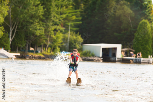 Fényképezés Child learning to water skiing on a lake