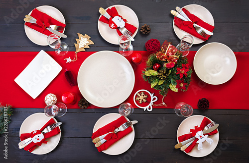 Prepared Christmas table for serving dishes. Scenery, spruce branches, tinsel and candles. Top view