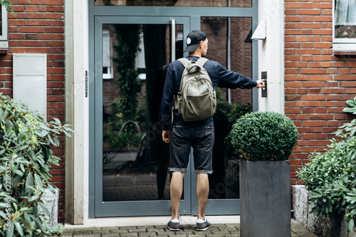 Fotografie, Obraz  The tourist rings the doorbell to check in to the room he has booked or the student with the backpack returns home after classes at the institute or on vacation