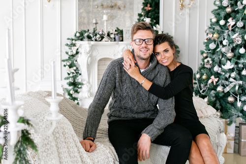 young couple happy family having fun at home christmas morning in bright living room